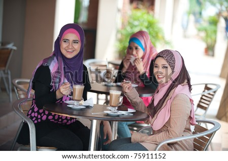 young muslim woman in head scarf drink in cafe with friends