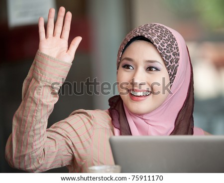 young muslim woman in head scarf say hi to friend in cafe - stock photo