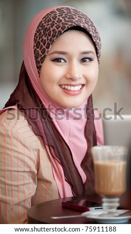 young muslim woman in head scarf smile in cafe - stock photo