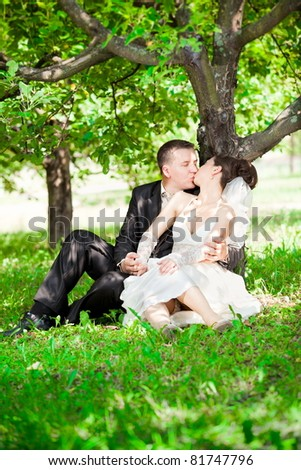 Young newly married couple kissing under tree in forest