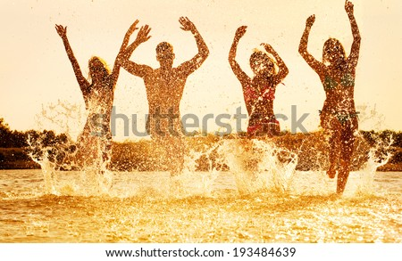 young people dancing and spraying at the beach on  beautiful summer sunset