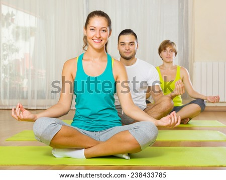 young people doing yoga on mats in gym - stock photo