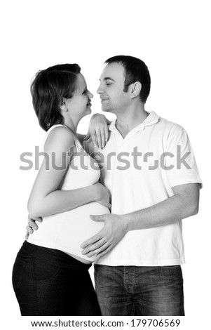 Young pregnant woman and man,looking at each other. Pregnant family. Studio shot - stock photo