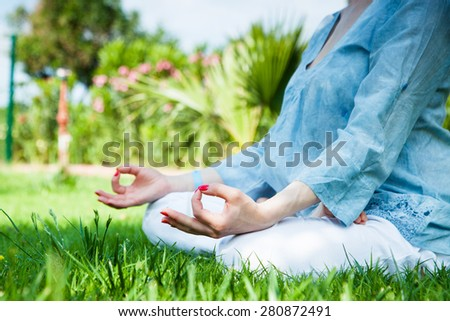 Young pretty woman doing yoga exercise outdoor.  - stock photo