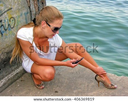 young pretty woman sitting alone on the pier near the sea and sending message  on mobile  - stock photo