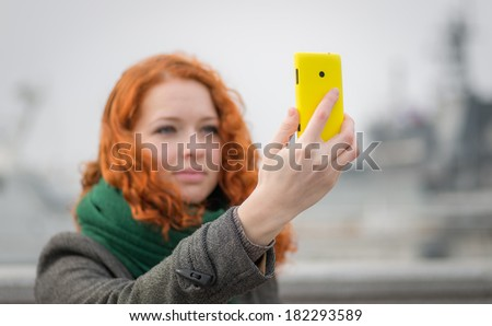 Young redhead girl taking a selfie outdoors on sunny day.  - stock photo