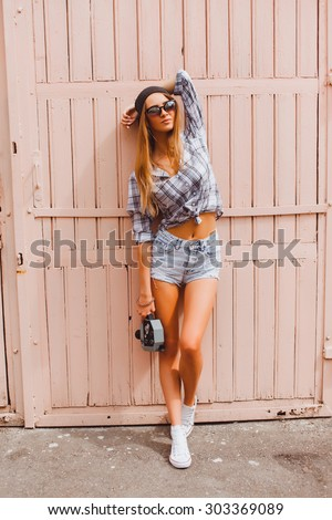 Young sexy blonde woman posing on the wall,wearing, swag hat mirrored sunglasses and bright make up, holding vintage camera, Lifestyle portrait bright toned colors,hight heels   - stock photo