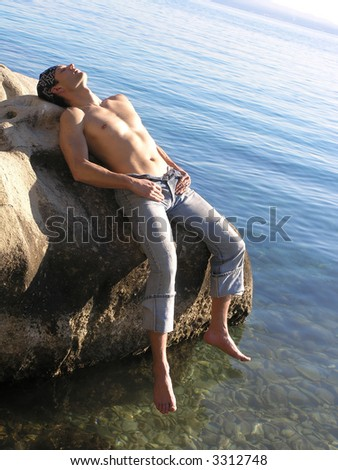 Young sexy man at the beach. - stock photo
