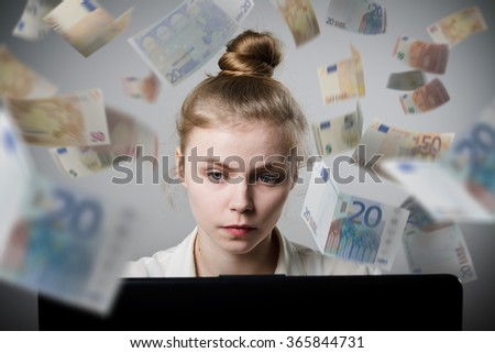 Young slim woman using a laptop to browse the net. Woman earns money on the internet. - stock photo