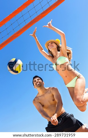 Young smiling couple playing volleyball on the beach in honeymoon - stock photo