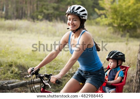 young smiling  mom with her son ride in the woods.