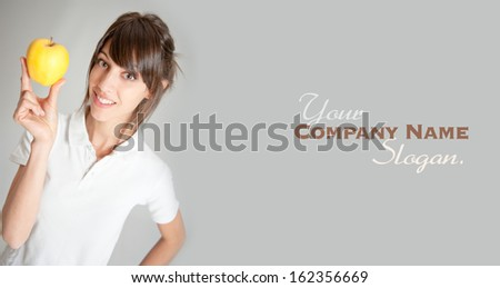 Young smiling woman holding a golden apple  - stock photo