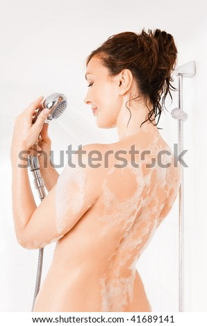 Young smiling woman taking a shower - stock photo