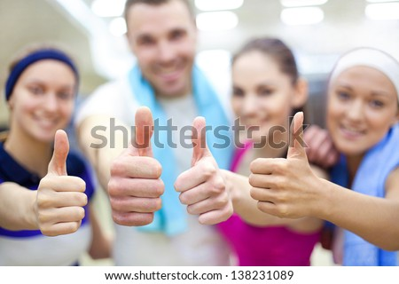 "young sporty people show ""OK""  in gym - stock photo"