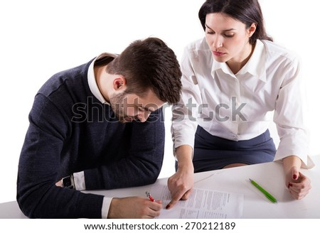 young student girl showing to young boy where to sign sitting at table