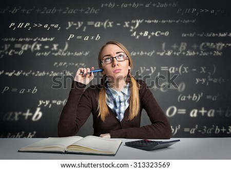 Young student with  thoughtful expression sitting at a desk with math formulas over her head  - stock photo