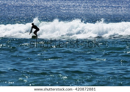 Young surfer surfing at Bondi beach. - stock photo