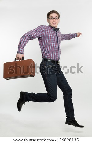 Young the man in glasses jumps with a suitcase