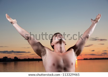 Young the man pulls hands to the sky - stock photo
