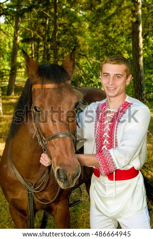 young Ukrainian with a horse in the forest
