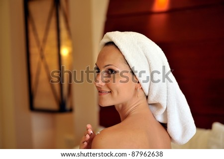 young woman applying cream on her body - stock photo