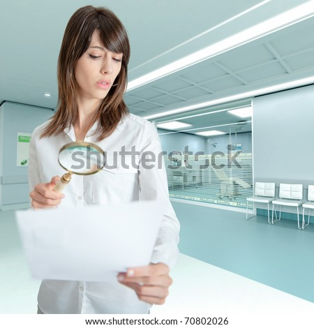 Young woman at the hospital examining a document with a magnifying glass - stock photo
