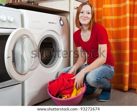 Young woman doing laundry at her home - stock photo