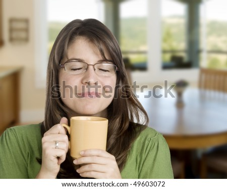 young woman enjoying here cup of coffee, indoors - stock photo