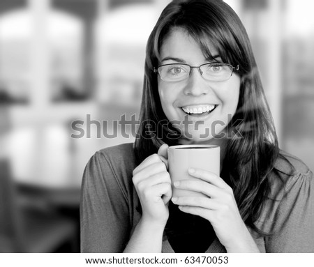 young woman enjoying here cup of coffee, indoors, visible steam coming from cup - stock photo
