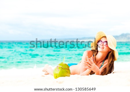 young woman in bikini and straw hat with fresh coconut
