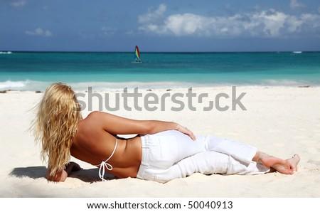 Young woman in bikini enjoying the day at the Caribbean beach - stock photo