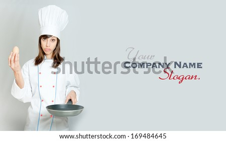Young woman in chef's attire with funny expression with an egg and a frying pan  - stock photo