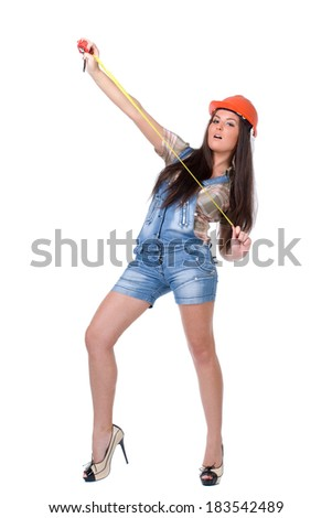 Young woman in orange helmet and jeans holding tape measure tool. Over white background.