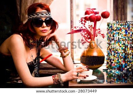 young woman in summer clothes and sunglasses drinking coffee in a restaurant - stock photo