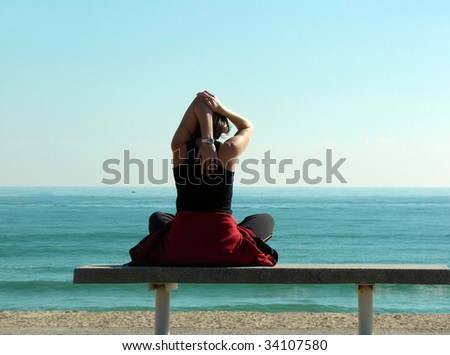 young woman is engaged in yoga on a beach of Mediterranean sea - stock photo