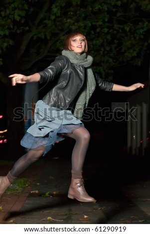 young woman jumping over a puddle