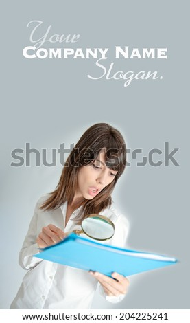 Young woman looking to a file through a magnifying glass with a shocked expression   - stock photo