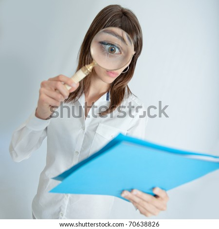 Young woman looking to a file through a magnifying glass with a shocked expression