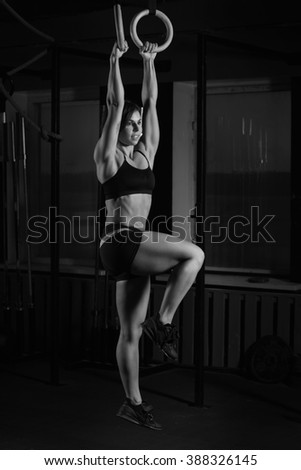 young woman on gymnast rings in the gym