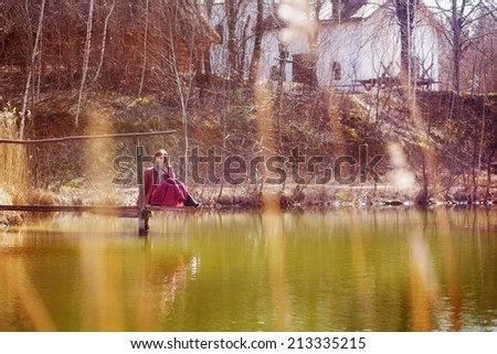 young woman on wooden pier at the lake  - stock photo