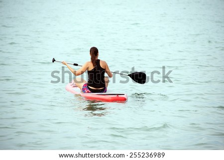 Young woman paddleboarding on a lake - stock photo