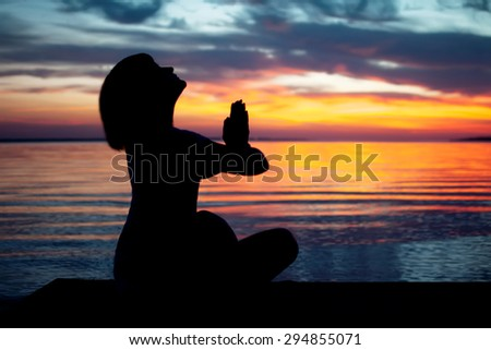 young woman practicing yoga on the ocean  beach . natural summer background with beautiful sunset - stock photo
