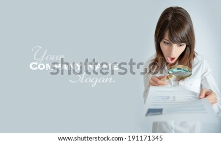 Young woman reading a document through a magnifying glass with a shocked expression   - stock photo