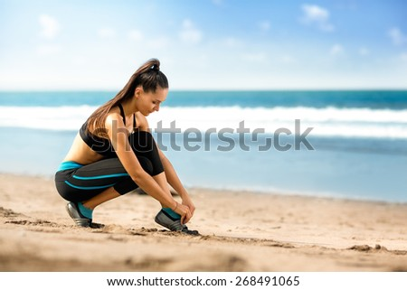 young woman runner tying shoelaces, girl doing sport outdoor