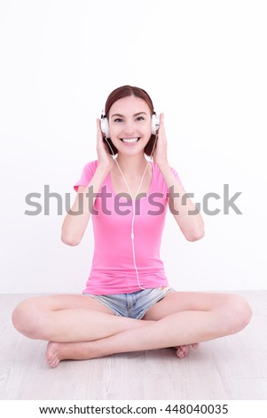 young woman sit listen music and smile , caucasian