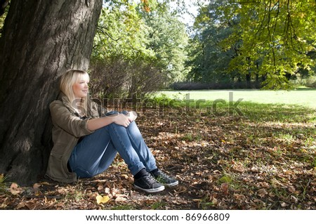 young woman sitting in the park - stock photo