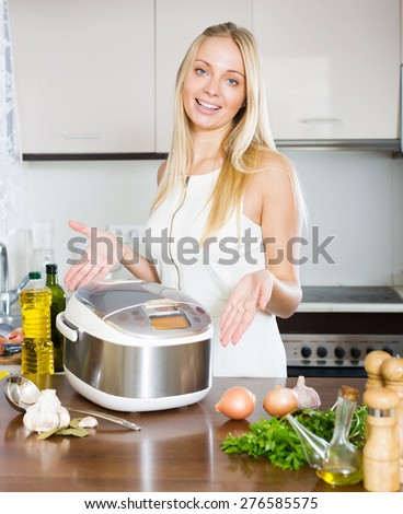 young woman using new  slo-cooker at home - stock photo