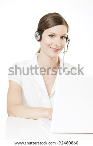 : Young woman with a white blouse and a white laptop is smiling at the camera, wearing a headset with a microphone for taking calls.