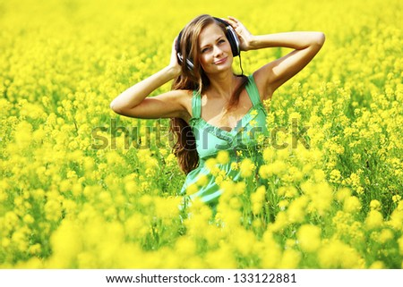 Young woman with headphones listening to music on oilseed flowering field - stock photo