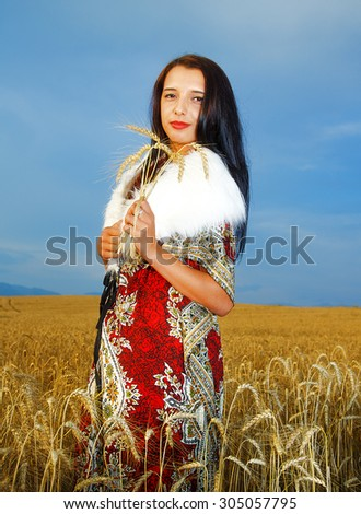 Young woman with ornamental dress and white fur standing on a wheat field with sunset. Natural background. - stock photo